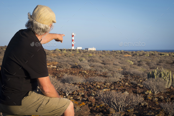 Adult senior man with cap indicates the light house on the cliff, tropical area with volcanic rocks - Stock Photo - Images