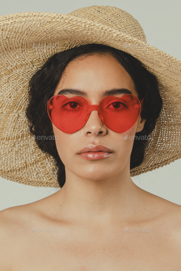 Bare chested woman wearing a big round hat and red vintage heart-shaped sunglasses - Stock Photo - Images