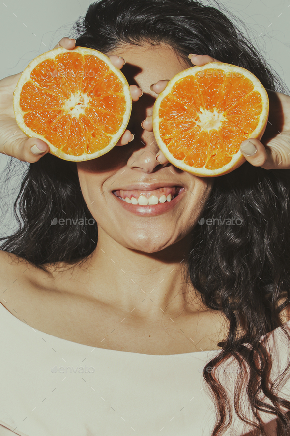 Cheerful woman with sliced oranges covering her eyes - Stock Photo - Images