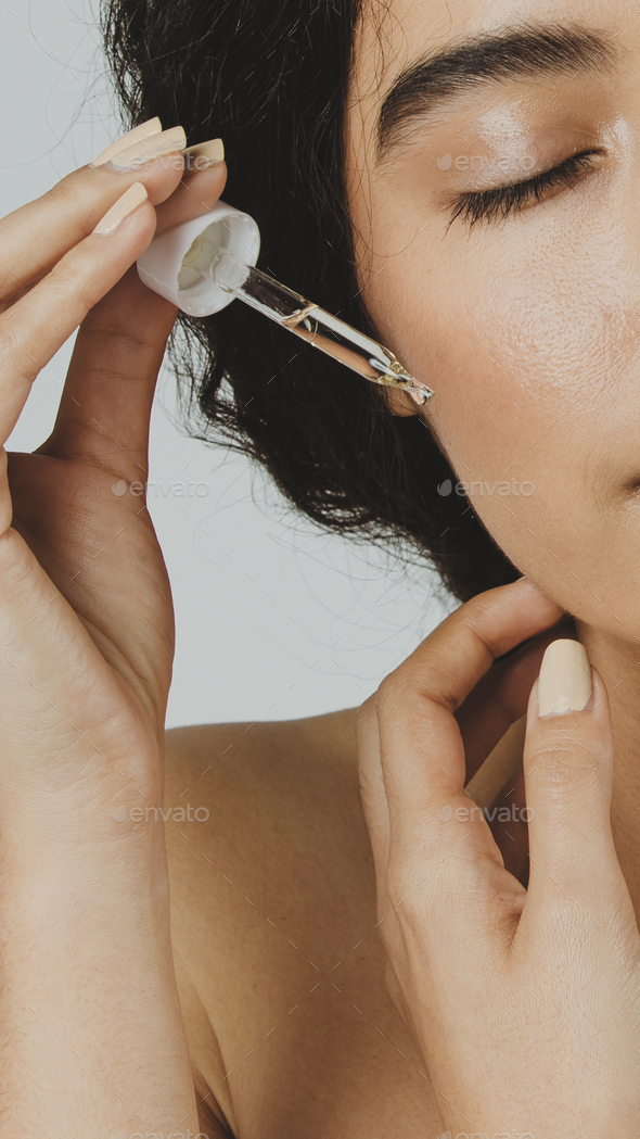 Young woman applying serum on her face - Stock Photo - Images