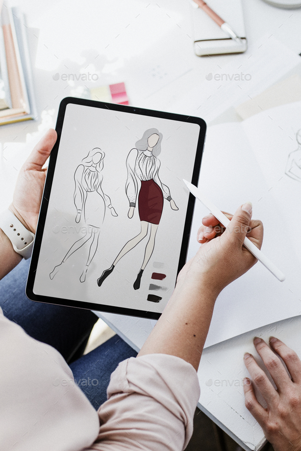 Fashion designer drawing on a digital tablet - Stock Photo - Images