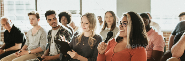 Cheerful woman speaking on a microphone in a workshop - Stock Photo - Images