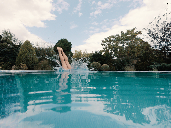 Slender girl dives into the pool - Stock Photo - Images