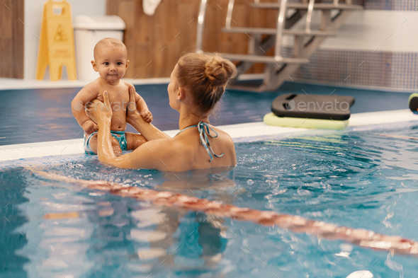 Mother and little son having fun in a swimming pool - Stock Photo - Images