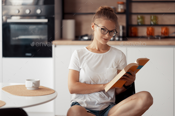 Cute girl is drinking coffee and reading a book - Stock Photo - Images