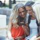 Three female friends with smartphone having fun in social media - PhotoDune Item for Sale