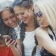 Girlfriends using smartphone and having fun in social media - PhotoDune Item for Sale