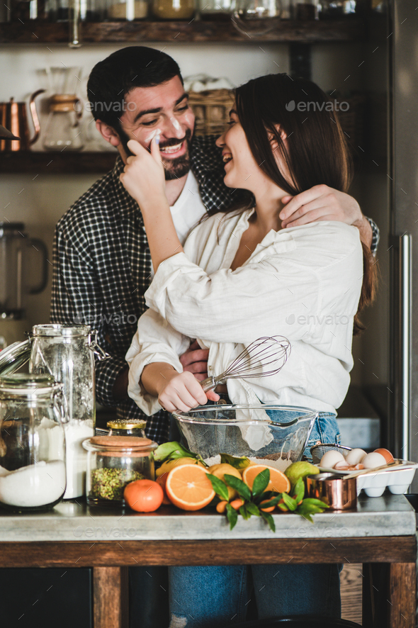 Young happy couple baking pie together for Valentines day - Stock Photo - Images