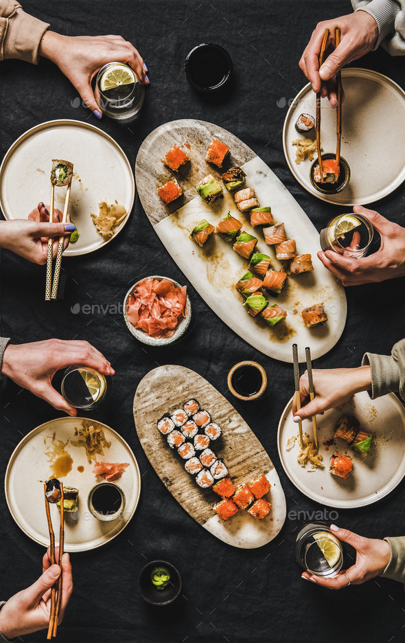 Flat-lay of people eating various sushi during japanese lockdown dinner - Stock Photo - Images