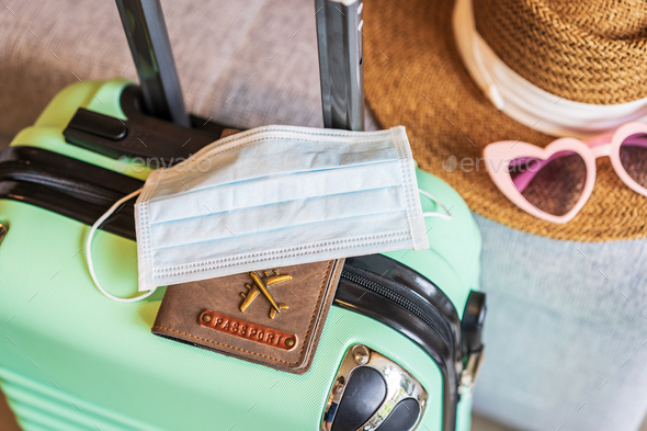 Medical mask with passport and luggage prepare for a new normal lifestyle traveling - Stock Photo - Images