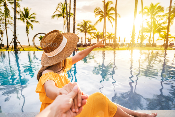 Young couple traveler relaxing and enjoying the sunset by a tropical resort pool - Stock Photo - Images