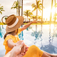 Young couple traveler relaxing and enjoying the sunset by a tropical resort pool - PhotoDune Item for Sale