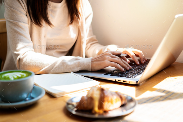 Young woman with cup of coffee sitting and working on laptop at coffee shop - Stock Photo - Images