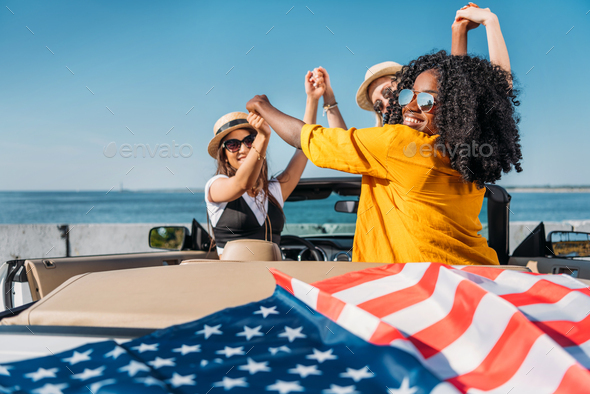 multiethnic women holding hands while sitting in car with american flag at seaside - Stock Photo - Images