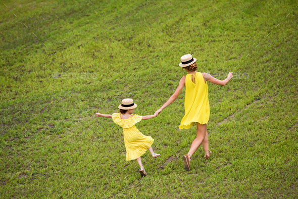 back view of pretty mother and daughter in yellow dresses holding hands while walking on green lawn - Stock Photo - Images