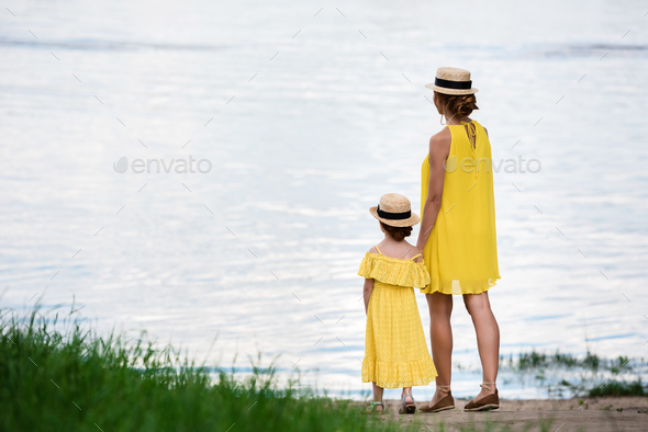 back view of pretty mother and daughter holding hands while standing at riverside - Stock Photo - Images