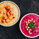 Beet hummus and classic hummus with crisp bread in bowls on dark stone background. - PhotoDune Item for Sale
