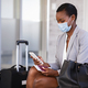 Business woman in airport with face mask checking phone - PhotoDune Item for Sale