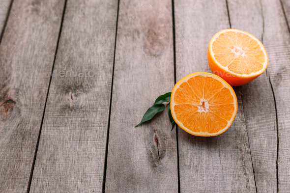 Halves of orange fruit on gray wooden background. Orange pulp and green leaves - Stock Photo - Images
