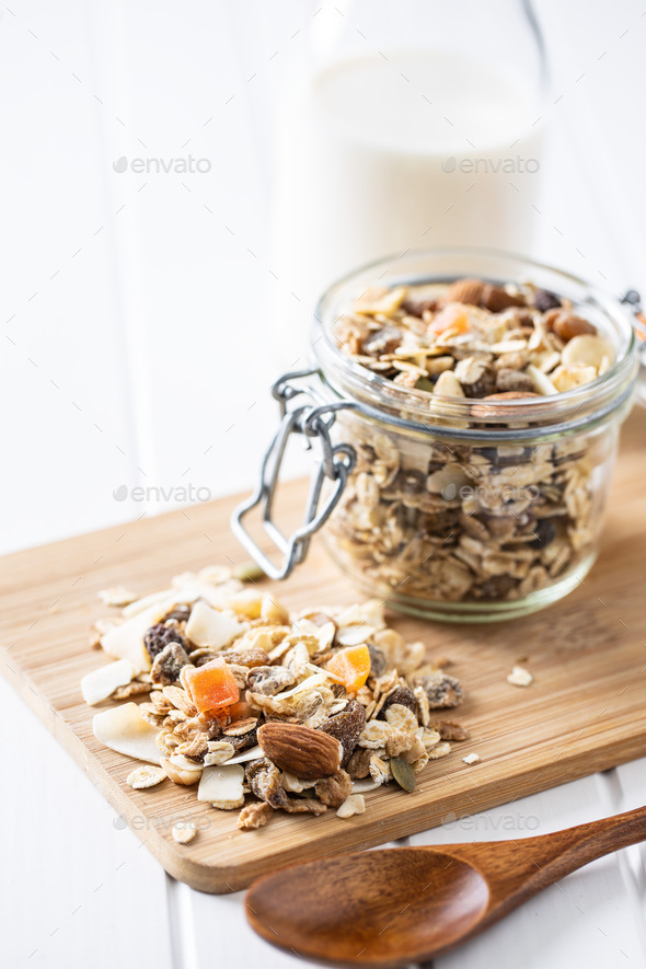 Beakfast cereals on cutting board. Healthy muesli with oat flakes, nuts and raisins - Stock Photo - Images
