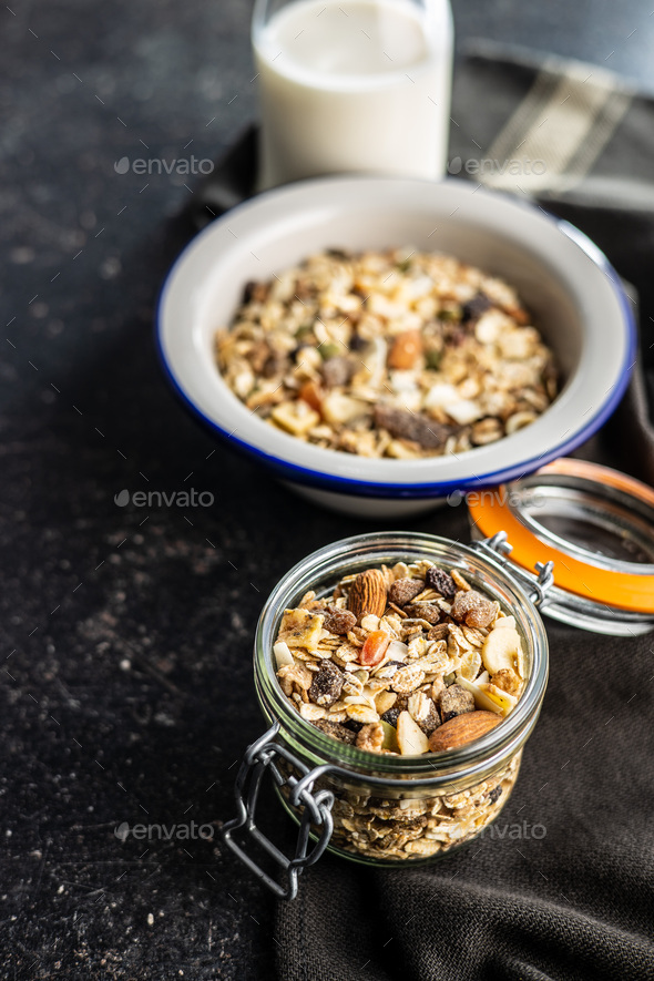 Beakfast cereals in jar. Healthy muesli with oat flakes, nuts and raisins - Stock Photo - Images