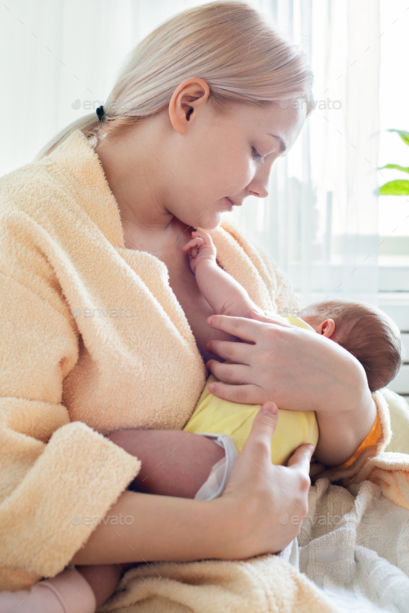 Caucasian blonde young mother breastfeeding her baby - Stock Photo - Images