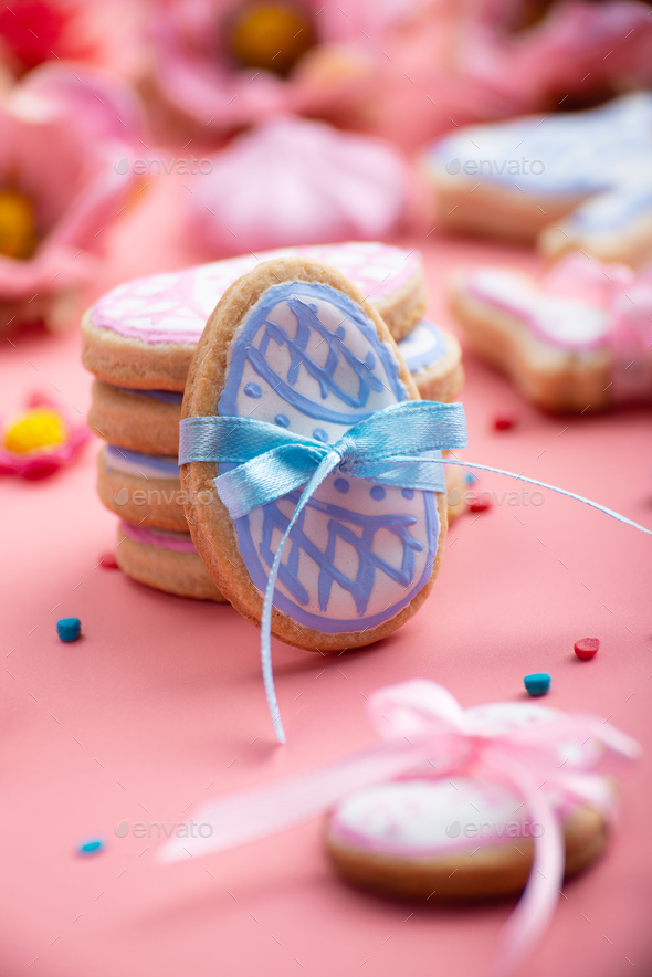 Easter baking background of frosted cookies in shape of egg on pink background - Stock Photo - Images