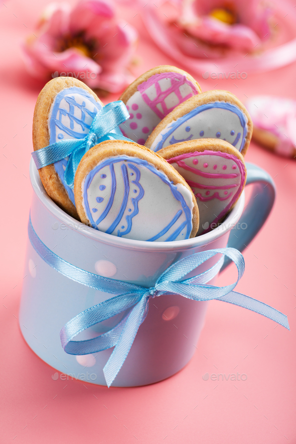 Easter baking background of frosted cookies in shape of egg in blue mug on pink background - Stock Photo - Images
