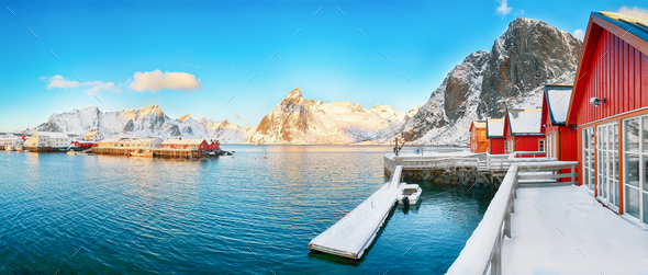 Traditional Norwegian red wooden houses (rorbuer) on the shore of  Reinefjorden near Hamnoy village. - Stock Photo - Images