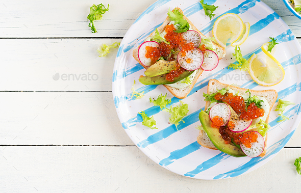 Sandwiches with salmon red caviar with sliced avocado and radish. - Stock Photo - Images