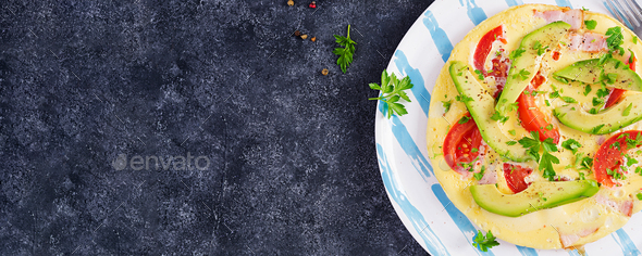 Omelette with ham,  tomatoes and avocado on grey table. - Stock Photo - Images