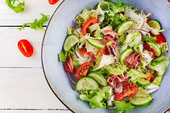 Ketogenic salad with prosciutto, tomatoes, cucumber, lettuce, red onion  and cheese - Stock Photo - Images