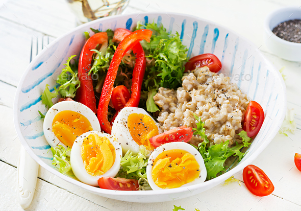 Breakfast oatmeal porridge with green herbs, boiled egg, tomatoes and paprika. - Stock Photo - Images