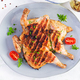 Grilled chicken Tabaka on blue plate. Georgian cuisine. Top view, above - PhotoDune Item for Sale