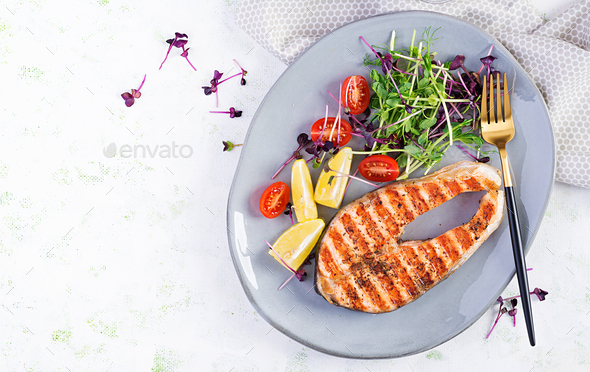 Salmon fish steak grilled and tomatoes salad with microgreens. - Stock Photo - Images