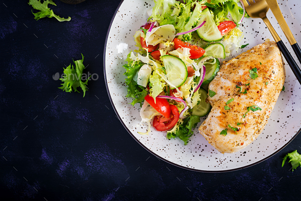 Fried chicken fillet and fresh vegetable salad of tomatoes, cucumbers and lettuce - Stock Photo - Images