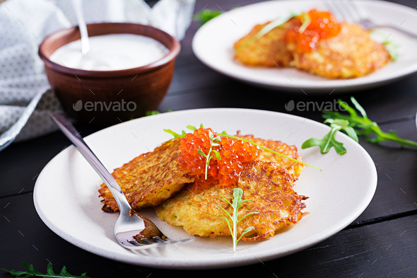Fried potato pancakes with red caviar and sour cream, fritter, roesti. - Stock Photo - Images