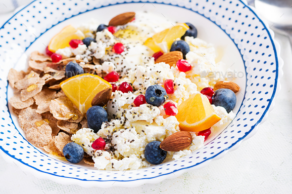 Bowl of flakes with cottage cheese and yogurt, blueberryes and pomegranate - Stock Photo - Images
