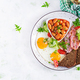 English breakfast - fried egg, beans, bacon, tomatoes  and bread. Top view, flat lay, overhead - PhotoDune Item for Sale