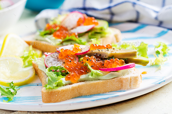 Sandwiches with salmon red caviar with sliced avocado and radish. Sandwich for lunch. Premium food - Stock Photo - Images