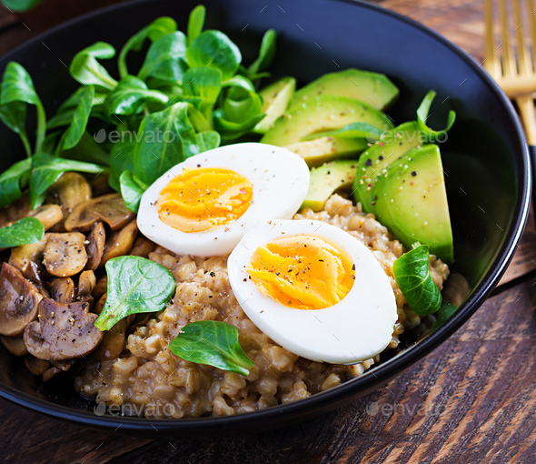 Breakfast oatmeal porridge with boiled egg, avocado and fried mushrooms. Healthy balanced food. - Stock Photo - Images