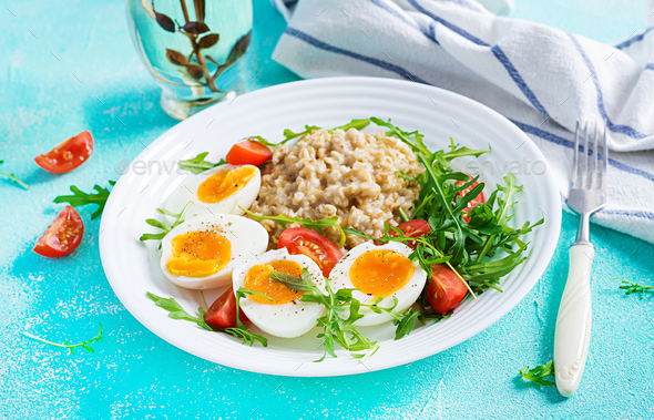 Breakfast oatmeal porridge with boiled egg, cherry tomatoes and arugula. Healthy balanced food. - Stock Photo - Images