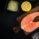 Raw fish salmon steak fillet with cooking ingredients, herbs and lemon on black background - PhotoDune Item for Sale