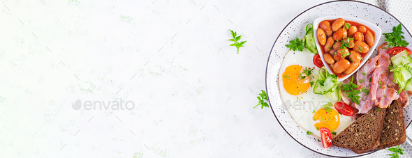English breakfast - fried egg, beans, bacon, tomatoes  and bread. Top view, banner, overhead - Stock Photo - Images
