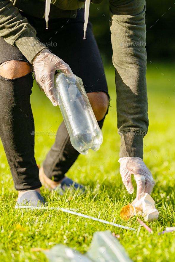 Low section of man cleaning park for plastic and trash on sunny day - Stock Photo - Images