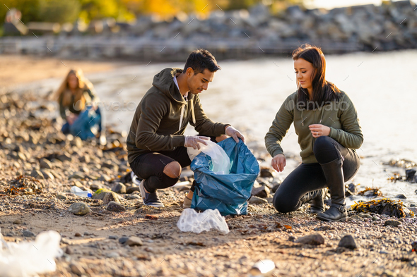 Team of hard working volunteers collecting plastic garbage at beach - Stock Photo - Images