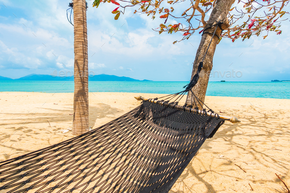 Empty hammock swing around beach sea ocean with white cloud blue sky - Stock Photo - Images