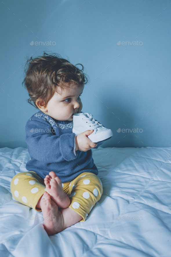 Little baby playing with a sneaker - Stock Photo - Images