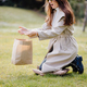 happy young woman holding craft bag present outdoors in park - PhotoDune Item for Sale