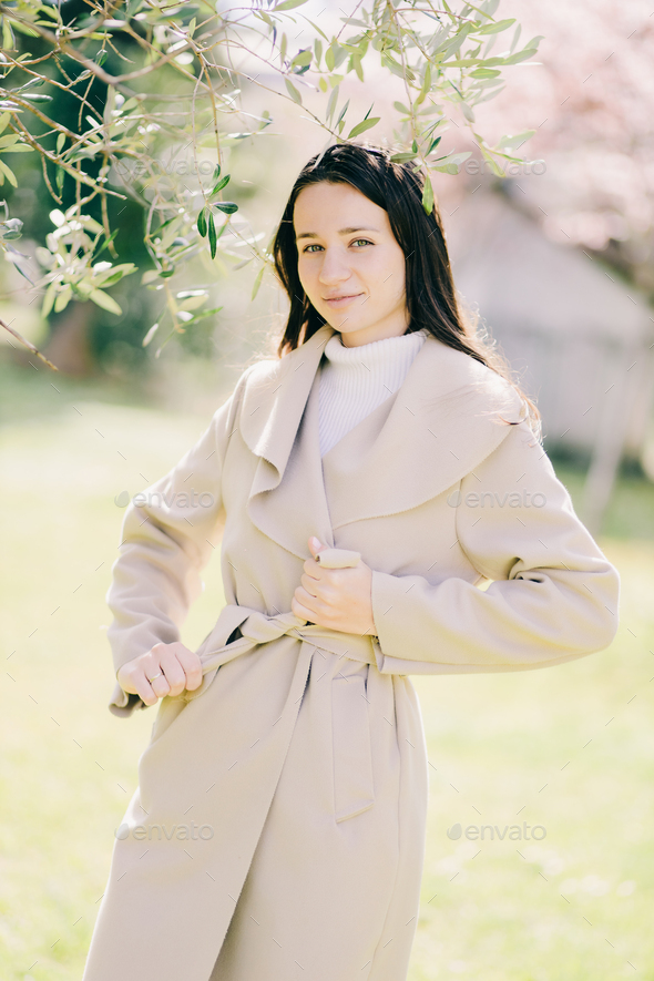 outdoor lifestyle fashion portrait of young woman wearing spring coat - Stock Photo - Images